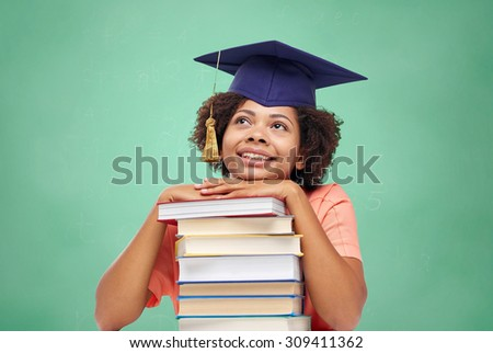 education, school, knowledge and people concept - happy smiling african american student girl in bachelor cap with books sitting at table and dreaming over green chalk board background - stock photo