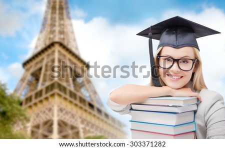 education, school, knowledge and people concept - picture of happy student girl or woman in trencher cap with stack of books over paris eiffel tower background - stock photo