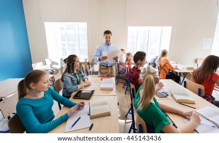 education, school, learning and people concept - group of students and teacher with test results in classroom - stock photo