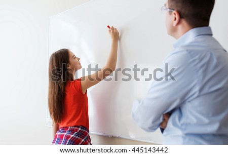 education, school, learning and people concept - student girl writing something on blank white board and teacher in classroom - stock photo