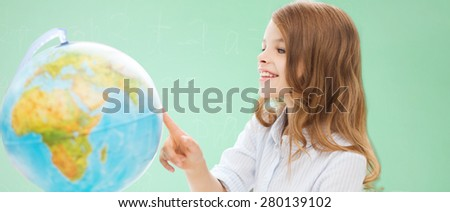 education, school, people, childhood and school concept - smiling little student girl with globe over green chalk board background - stock photo
