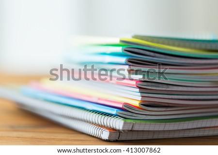 education, school supplies and object concept - close up of notebooks on wooden table