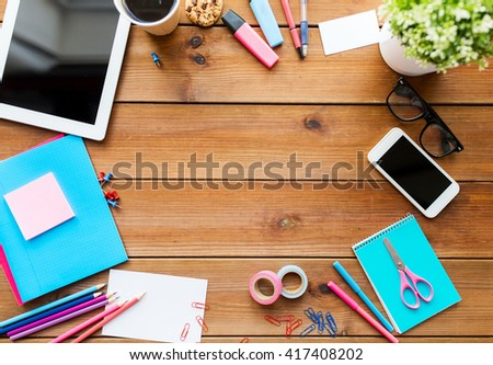 education, school supplies, art, creativity and object concept - close up of stationery and tablet pc computer with smartphone on wooden table - stock photo