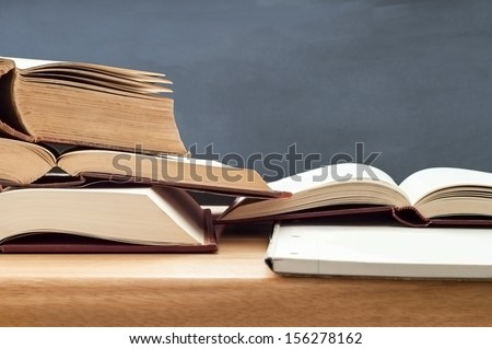 Education shot of stacked old books opened for study on wooden desk with blackboard in background. - stock photo
