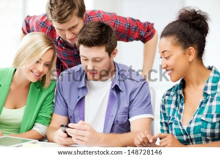 education, smatphones and internet - smiling students looking at smartphone at school