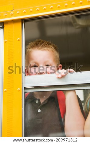 Education: Smiling Boy Student Peeks Out From School Bus Window