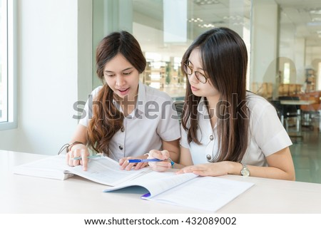 Education, Student, People concept - Two Asian students studying together at university.  Asian students looking happy to study. High school student.  - stock photo