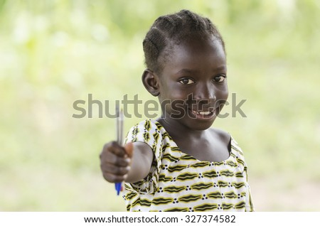 Education symbol: little African black teenage girl holding pen in the air lightly smiling to the camera. African children need education since it is the most important thing for a better future. - stock photo