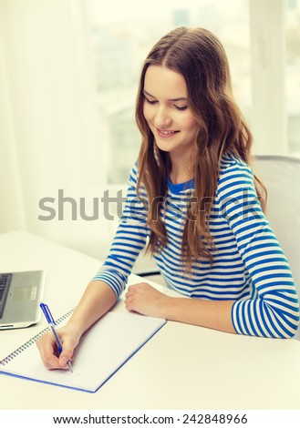education, technology and home concept - smiling teenage girl with laptop computer, notebook and pen at home - stock photo
