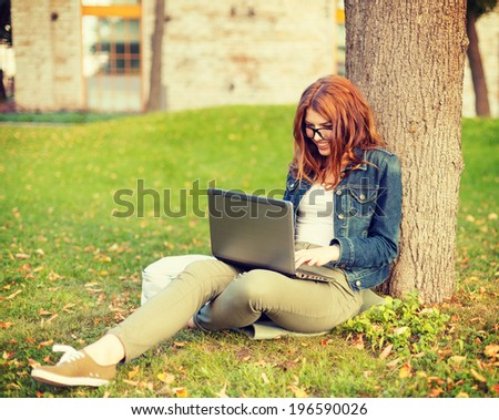 education, technology and internet concept - smiling redhead teenager in eyeglasses with laptop computer - stock photo