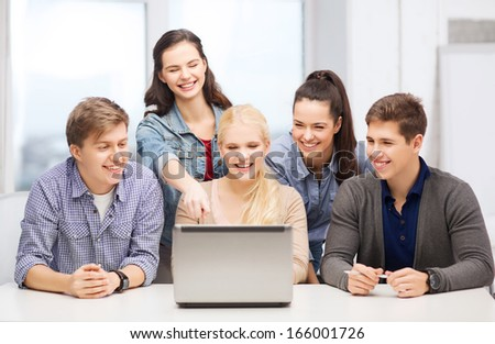 education, technology and internet concept - smiling students looking and pointing at laptop at school - stock photo