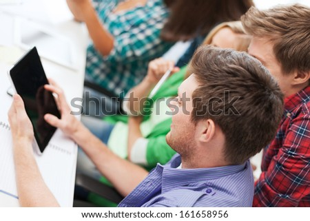 education, technology and internet concept - smiling students looking at tablet pc at school - stock photo
