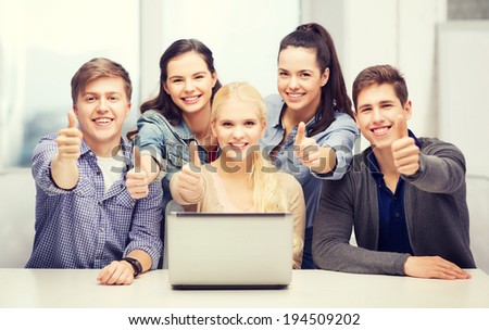 education, technology and internet concept - smiling students with laptop showing thumbs up at school - stock photo