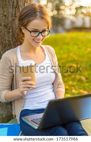 education, technology and internet concept - smiling teenager in eyeglasses with laptop computer and take away coffee or tea - stock photo