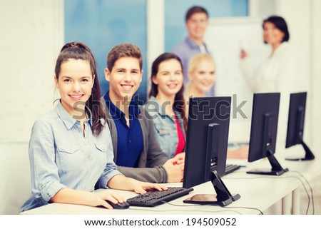 education, technology and internet concept - students looking at computer monitor at school - stock photo