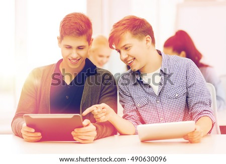 education, technology and internet - two smiling students looking at tablet pc in lecture at school