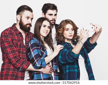 education, technology and people concept: group of students taking selfie with smartphone  over white background.Special Fashionable toning. - stock photo