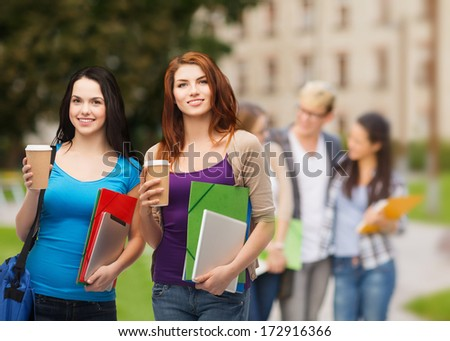 education, technology and people concept - two smiling students with bag, folders, tablet pc and takeaway coffee standing