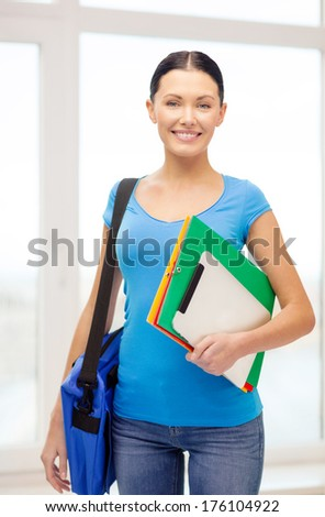 education, technology and school concept - smiling female student with folders, tablet pc and bag at school - stock photo
