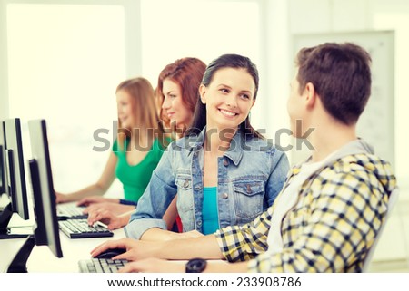 education, technology and school concept - smiling students in computer class at school having discussion