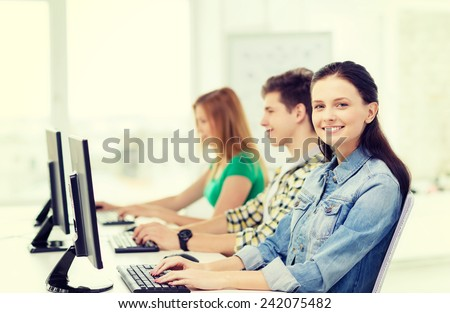 education, technology and school concept - three smiling students in computer class - stock photo