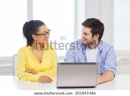 education, technology, business, startup and office concept - two smiling people with laptop in office
