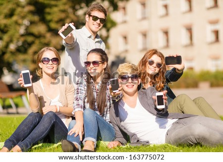 education, technology, internet, summer holidays, social networking and teenage concept - group of teenagers with smartphones - stock photo