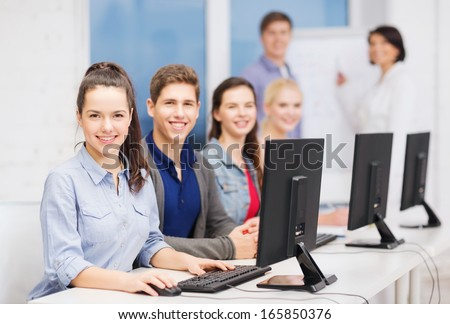 education, techology and internet concept - group of smiling students with computer monitor at school - stock photo