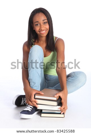 Education time for pretty young African American teenager school girl student with big beautiful smile, sitting on floor wearing blue jeans and vest holding school study books. - stock photo