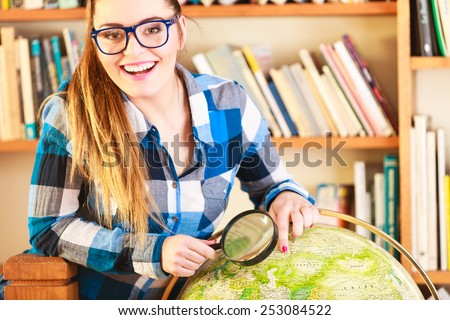 Education travel and geography concept. Young clever woman female student in blue glasses in library with globe and magnifying glass - stock photo