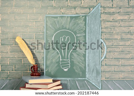 Education unusual concept on chalkboard and books with quill pen - stock photo