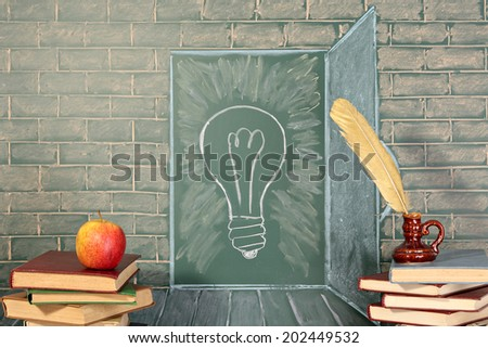 Education unusual concept on chalkboard and books with quill pen and apple - stock photo