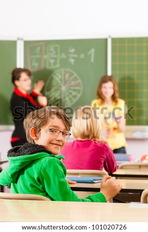 Education - Young female teacher with pupil in his form of the elementary or primary school teaching - stock photo