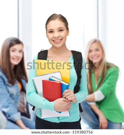 education, youth, school, teamwork concept - smiling student with books and schoolbag - stock photo