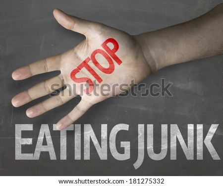 Educational and Creative composition with the message Stop Eating Junk on the blackboard - stock photo