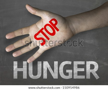 Educational and Creative composition with the message Stop Hunger on the blackboard - stock photo