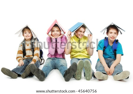 Educational theme: group of teenagers sitting together and holding books on their heads. - stock photo