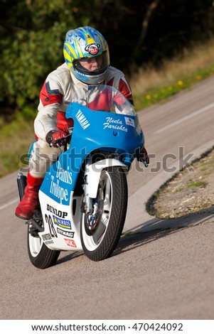 EELMORE, UK - SEPTEMBER 29: An unnamed rider competing in the VMCC Eelmore sprint race takes the top corner of the circuit at speed on his vintage Yamaha motorcycle on September 29, 2013 in Eelmore