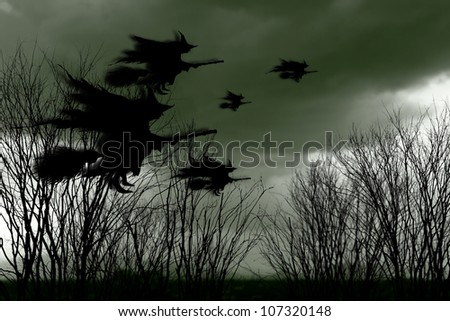 Eerie surreal silhouette of a swarm of witches on broomsticks flying across a spooky landscape with dead trees for Halloween concept.