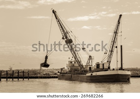 Effect vintage. Small dredge marine, which is cleaning a navigation channel - stock photo