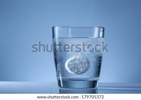 effervescent tablet in a glass of water - stock photo