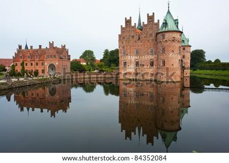 Egeskov castle slot landmark fairy tale castle in Funen Denmark view from the lake - stock photo