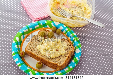 Egg and olive mixture in plastic bowl being spread over 12-grain bread on paper picnic plate.  Decorated with stuffed olives. - stock photo
