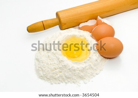 Egg in a pile of flour with other eggs and kitchen utensils - stock photo