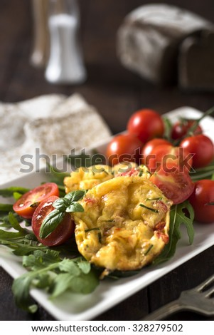 Egg muffins with tomatoes and arugula - stock photo