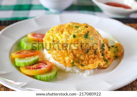 Egg omelet, Omelet Thai style on top of rice white plate and Cucumber tomato served with chili sauce - Traditional Thai Food - stock photo