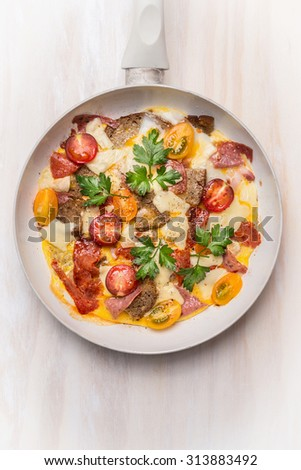 Egg omelette in white frypan with tomatoes,bread, cheese and sausage on white wooden background, top view, close up - stock photo