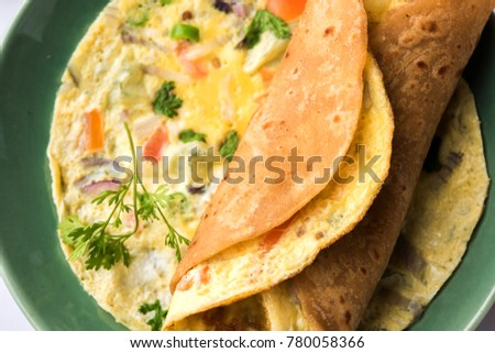 Egg omlet / Omelette chapati roll or Indian bread or roti rolled with omlet. Popular, quick and healthy recipe for kid's tiffin or lunch box