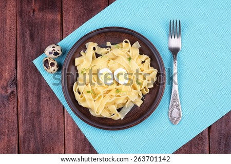 Egg pasta with quail egg and watercress salad. Pasta and watercress salad on the table. Delicious hearty lunch. Top view. Pasta dish. Healthy food. - stock photo