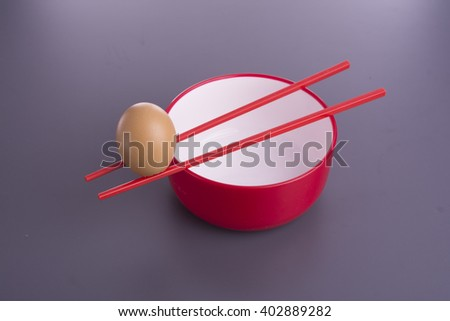 Egg,red bowl with  red chop sticks on purple table - stock photo
